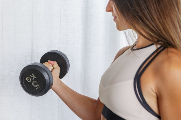 Przytnij sportsmenkę ćwicząc z hantlami w domu