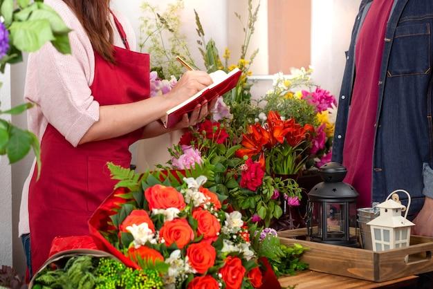 Przytnij widok sprzedawcy kwiatów przyjmujących zamówienie. biznes florystyczny. układ bukietów.