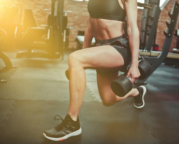 Przytnij zdjęcie dopasuj dziewczyna robi ćwiczenia rzuca się z hantlami w ręce na siłowni