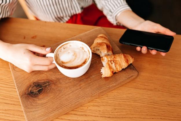 Przytnij zdjęcie filiżanki z kawą i francuskimi rogalikami na drewnianym biurku.