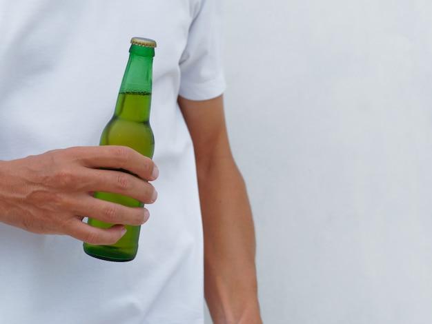 Przytnij zdjęcie. mężczyzna w białej koszulce, trzymając butelkę piwa. skopiuj miejsce