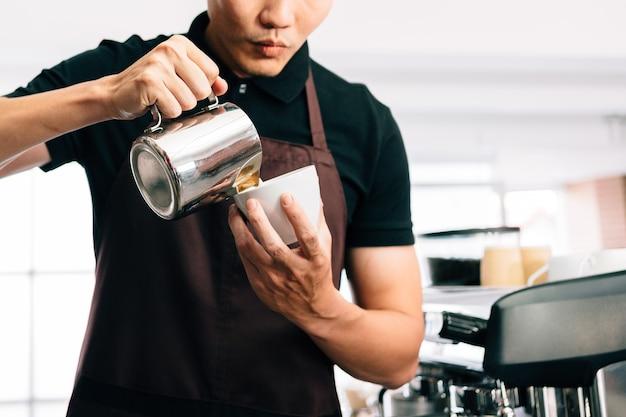Przytnij zdjęcie młodego baristy w fartuchu, wlewającego gorące mleko do czarnej kawy espresso w celu zrobienia latte art.