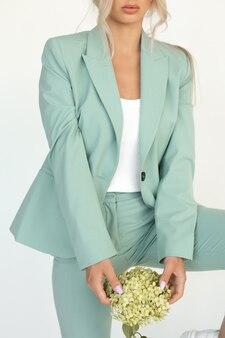 Przytnij zdjęcie młodej blondynki w miętowych spodniach z hortensją w dłoniach. zdjęcie wysokiej jakości