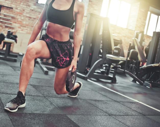 Przytnij zdjęcie szczupła sportowa brunetka robi noga rzuca ćwiczenia ze sztangą w rękach siłowni.