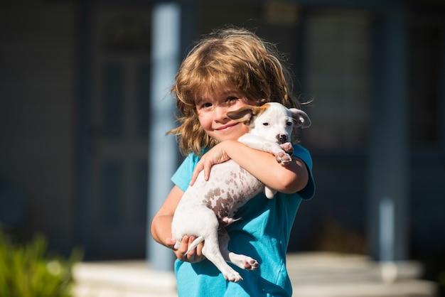 Przytul przyjaciół, przytulający się piesek. szczęśliwe dziecko i szczeniak przytula się z czułością uśmiechając się.