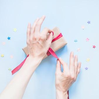 Przytul ręce wiążące wstążkę na prezent