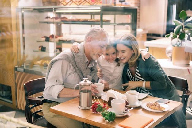 Przytulanie dziadków. kochająca wnuczka na sobie białą koszulę przytulanie jej kochających uśmiechniętych dziadków