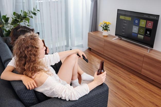 Przytulanie młodej pary pijącej piwo i oglądając nowy odcinek programu w domu