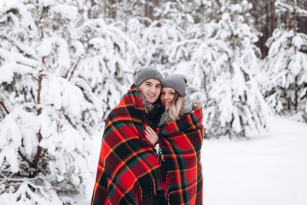 Przytulanie para patrząc na kamery z uśmiechem w śnieżnym lesie zima