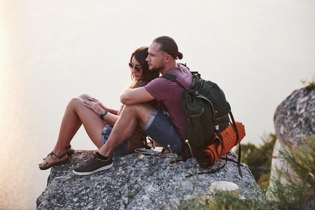 Przytulanie para z plecakiem siedząc na szczycie skały, ciesząc się widokiem wybrzeża rzeki lub jeziora.