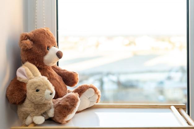 Przytulanie para zabawek. królik i miś obejmująca kochająca zabawka pluszowego misia i króliczek siedzący na parapecie