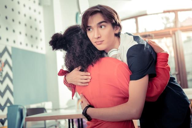 Przytulanie przyjaciela. przyjazny chłopak nastolatek przytulając swoją koleżankę