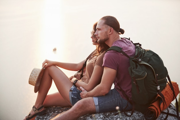 Przytulanie się para z plecakiem siedzi przy ognisku na szczycie góry