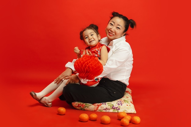 Przytulanie, uśmiechanie się szczęśliwe, trzymanie lampionów. . azjatycki portret matki i córki na czerwonej ścianie w tradycyjnej odzieży. świętowanie, ludzkie emocje, święta. copyspace.