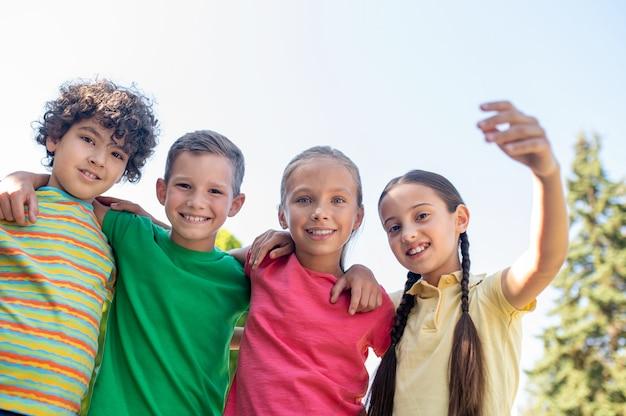 Przytulanie uśmiechniętych przyjaciół w wieku szkolnym na zewnątrz
