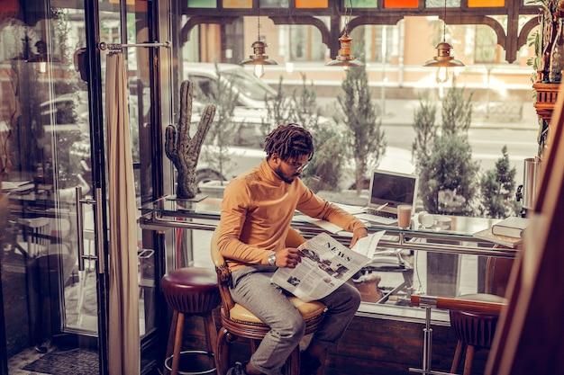 Przytulna atmosfera. poważny brodaty mężczyzna siedzi w półpozycji i czyta wiadomości
