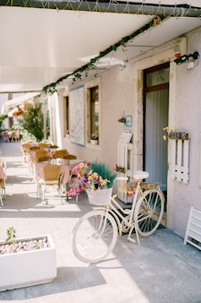 Przytulna biała kawiarnia ze stolikami dla gości i ozdobnym rowerem ozdobionym kwiatami przy wejściu