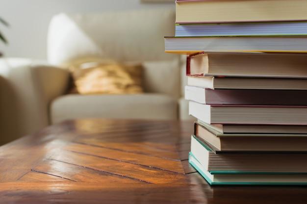 Przytulna dekoracja domu, biała skórzana kanapa, drewniany stół i poduszki. stos książek. czytanie koncepcji hobby.