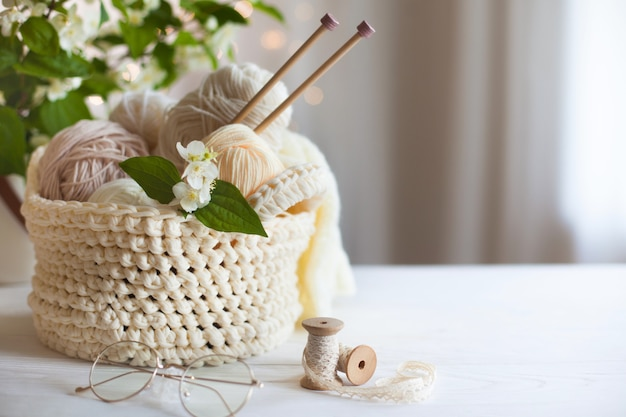 Przytulna domowa atmosfera. kobiece hobby dziewiarskie. przędza w ciepłych kolorach. różowy, brzoskwiniowy, beżowy, biały i zielony. początek procesu dziania swetra damskiego.