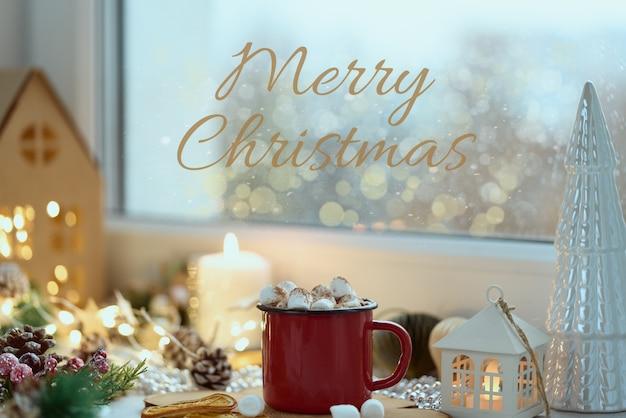 Przytulna domowa kartka świąteczna z tekstem wesołych świąt widok okna kubek gorącej czekolady na parapecie