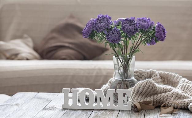 Przytulna domowa kompozycja z bukietem niebieskich chryzantem w szklanym wazonie i ozdobnym napisem home.