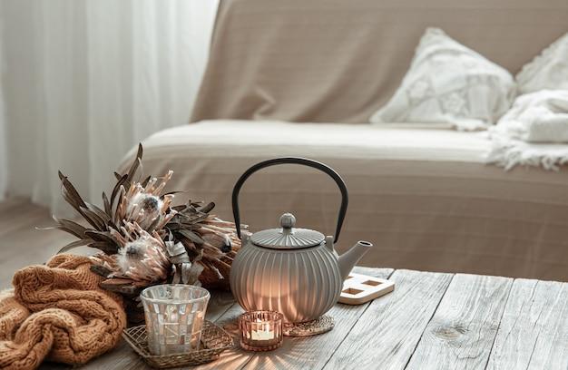 Przytulna domowa kompozycja z czajniczkiem i detalami wystroju we wnętrzu pokoju.