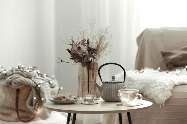 Przytulna domowa kompozycja z herbatą w domowym wnętrzu w stylu skandynawskim.