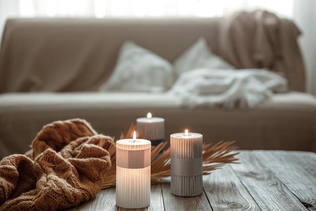 Przytulna domowa kompozycja z płonącymi świecami na drewnianym stole z dzianinowym elementem.