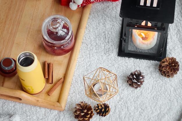 Przytulna domowa martwa natura: wełniane rękawiczki, czerwone wełniane skarpetki, rożki, świece z ciepłym wełnianym kocem i sweter. ferie