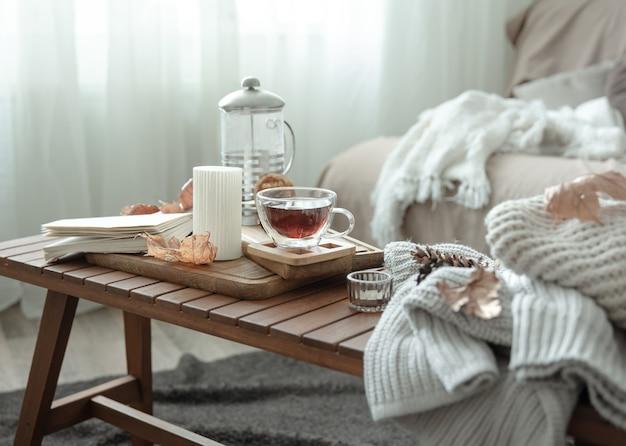 Przytulna domowa martwa natura z filiżanką herbaty i detalami jesiennego wystroju domu.