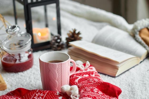 Przytulna domowa martwa natura z filiżanką herbaty i otwartą książką w ciepłą kratę. ferie