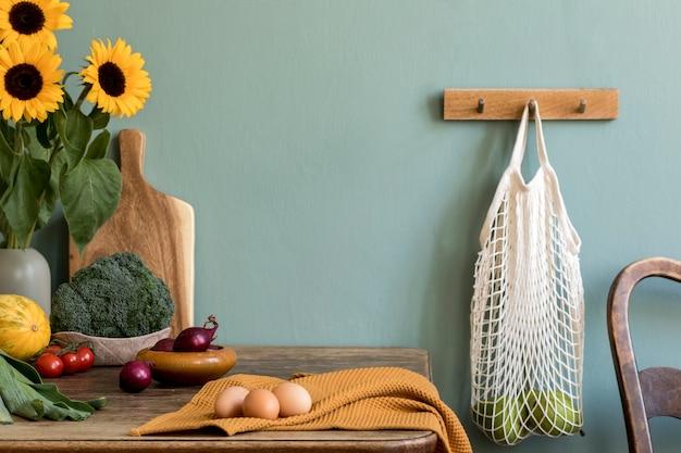 Przytulna i stylowa kompozycja kreatywnej jadalni z przestrzenią do kopiowania, drewnianą konsolą, słonecznikami i osobistymi dodatkami. zielona ściana. piękny i słoneczny poranek. szablon.