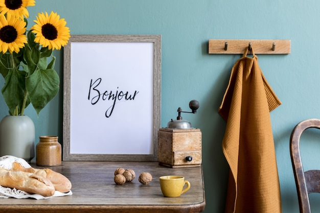 Przytulna i stylowa kompozycja kreatywnej jadalni z ramą garncarską, drewnianą konsolą, słonecznikami i osobistymi dodatkami. zielona ściana. piękny i słoneczny poranek.