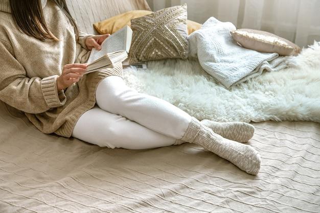 Przytulna jesień lub zima w domu, kobieta w swetrze z dzianiny i skarpetkach z książką w rękach.