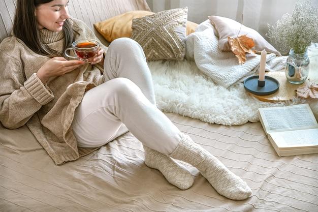 Przytulna jesień w domu, kobieta w swetrze z dzianiny przy filiżance herbaty.