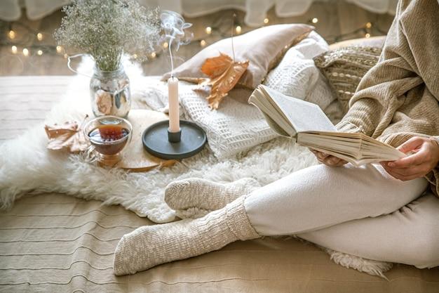Przytulna jesień w domu, kobieta z książką odpoczywa. przytulny styl życia. części ciała w kompozycji.