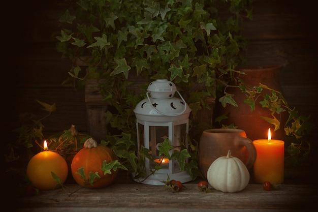 Przytulna jesień z dyniami, rustykalnymi ceramicznymi dzbankami, latarnią, świecami i bluszczem