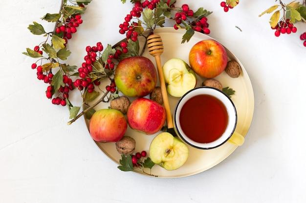 Przytulna jesienna, gorąca, przyprawiona herbata z miodem, jabłkami i czerwonymi jagodami głogu na tacy. martwa natura na białym tle. leżał płasko.