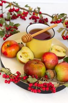Przytulna jesienna, gorąca, przyprawiona herbata z miodem, jabłkami i czerwonymi jagodami głogu na tacy. martwa natura na białym tle.