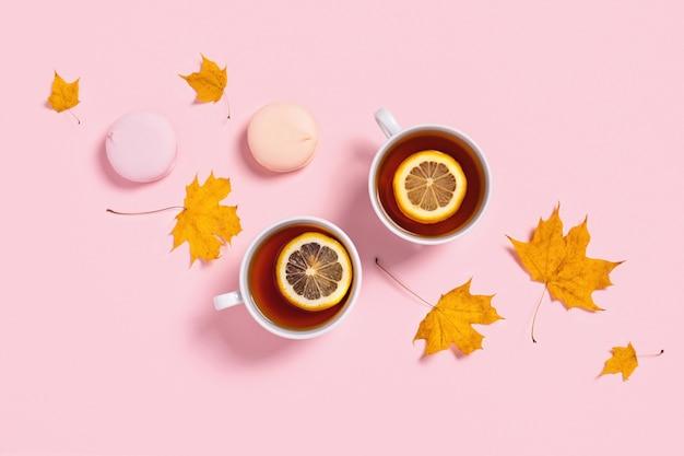 Przytulna jesienna kompozycja. dwie filiżanki herbaty z piankami i liśćmi klonu.
