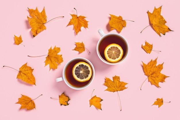 Przytulna jesienna kompozycja. dwie filiżanki herbaty z plasterkami cytryny i liści klonu.
