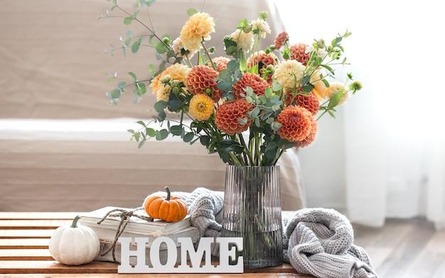 Przytulna jesienna kompozycja z bukietem chryzantem w wazonie, ozdobnym słowem home, dyniami i dzianinowym elementem na rozmytym tle, kopia przestrzeń.