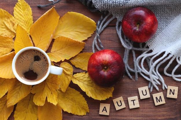 Przytulna jesienna kompozycja z filiżanką kawowych jabłek ciepłe jesienne liście w kratę i napis autumn