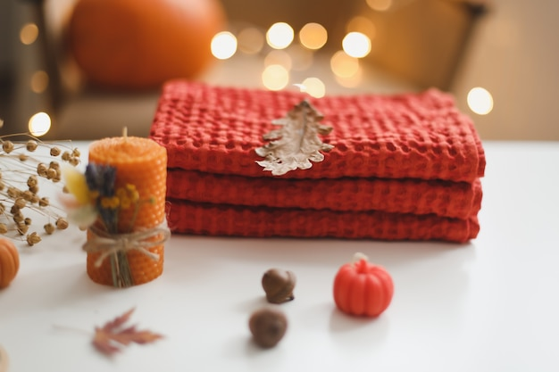 Przytulna jesienna kompozycja z liśćmi dyni i tekstyliami