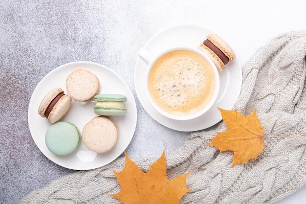 Przytulna jesienna kompozycja ze swetrem, kawą, różnymi makaronikami i żółtymi liśćmi klonu na kamiennym tle. układanie płaskie, widok z góry - obraz