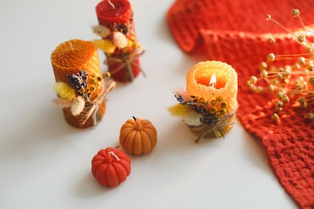 Przytulna jesienna kompozycja ze świecami z wosku dyniowego i liśćmi