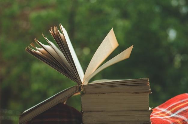 Przytulna jesienna martwa natura: filiżanka gorącej kawy i otwarta książka na parapecie z czerwonym kocem, dynią, szyszkami, świecami i deszczem na zewnątrz. jesień. apartament. deszcz