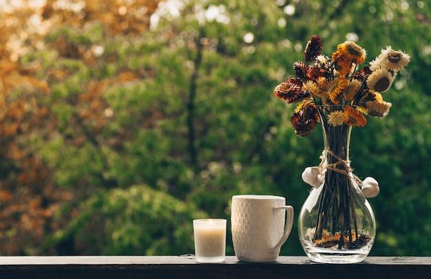 Przytulna jesienna martwa natura: filiżanka gorącej kawy z jesiennym bukietem kwiatów na parapecie vintage z szyszkami i deszczem na zewnątrz. jesień. apartament. deszcz