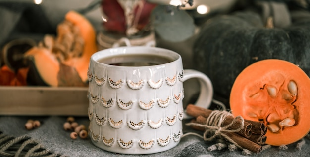 Przytulna jesienna martwa natura z filiżanką herbaty i dyni, z laskami cynamonu na ciepłej kracie, koncepcja na sezon jesienno-zimowy