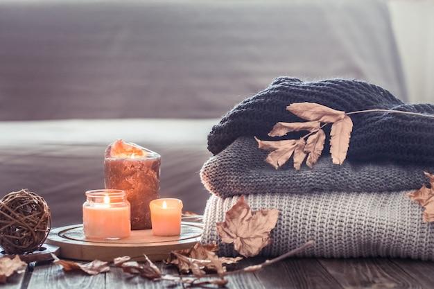 Przytulna jesienna martwa natura ze świecami i swetrem